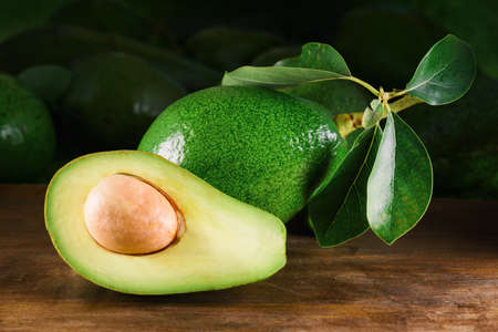 Fresh ripe green avocado with leaves on wooden table. Healthy eco food. Product of organic farming. Zdjęcie Seryjne - 125871342