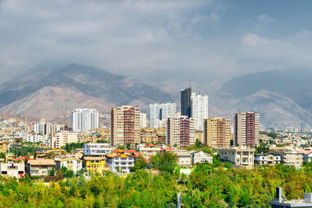 Beautiful view of Tehran, Iran. Mountains are visible in background. Residential buildings among green trees. Cityscape on sunny day. Tehran is a popular tourist destination of the Middle East.