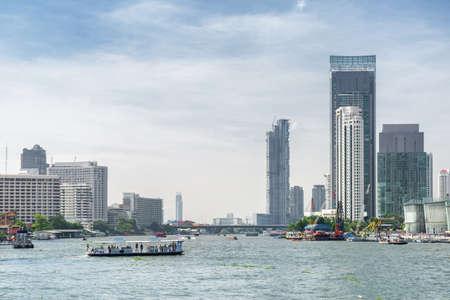 Ferry crossing the Chao Phraya River in Bangkok, Thailand. Unusual Bangkok skyline. Beautiful cityscape on sunny day.