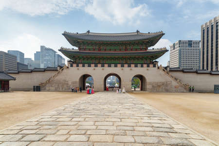 Amazing view of Gwanghwamun Gate from courtyard of Gyeongbokgung Palace at downtown of Seoul, South Korea. Modern buildings are visible on blue sky background. Seoul is a popular tourist destination. Zdjęcie Seryjne