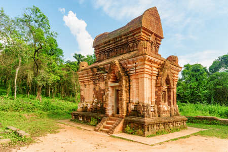 Awesome view of red brick temple of My Son Sanctuary among green woods in Da Nang (Danang), Vietnam. My Son is a complex of partially ruined ancient Hindu temples constructed by the kings of Champa.