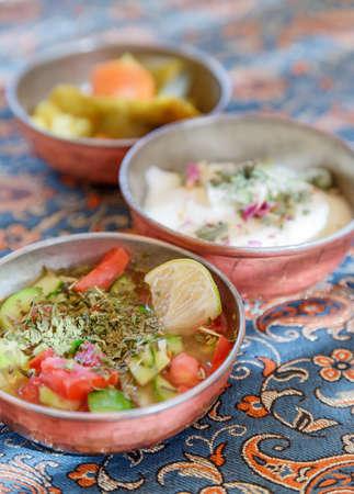 Traditional Iranian snacks. Fresh vegetable salad, yogurt and pickled vegetables. Persian cuisine. Focus on the salad.