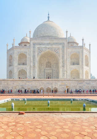 Scenic side view of the Taj Mahal on blue sky background, Agra, India. Visitors walking to the white marble mausoleum. The Taj Mahal is a popular tourist attraction of South Asia. Mughal architecture. Zdjęcie Seryjne
