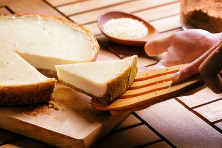 Hands taking piece of delicious freshly baked cheesecake. Homemade sweet dessert on wooden table. Food for all family. Zdjęcie Seryjne