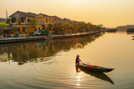 Awesome view of Vietnamese woman in traditional bamboo hat on wooden boat on the Thu Bon River at Hoi An Ancient Town at sunrise in Vietnam. Hoian is a popular tourist destination of Asia. Zdjęcie Seryjne