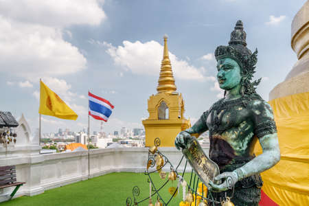 View of Buddhist statue at Wat Saket temple on the Golden Mount on blue sky background. The flag of the Kingdom of Thailand and Buddhist flag fluttering over Bangkok.