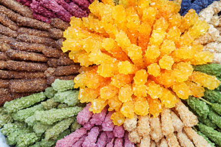 Top view of colored rock candies. Traditional Persian crystallized sugar in confectionery shop of Isfahan, Iran. Nabat (misri) is a part of the tea culture of the Middle East, India and Central Asia. Zdjęcie Seryjne - 125871758