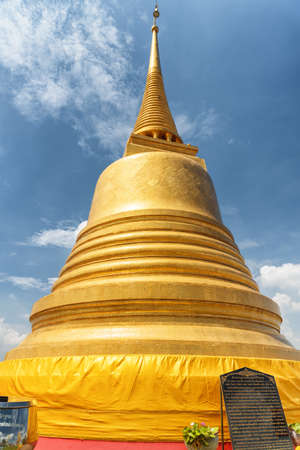 Bangkok, Thailand - 14 October, 2018: Bottom view of Gilded Buddhist Stupa at Wat Saket temple on the Golden Mount on blue sky background. Wat Saket temple is a popular tourist attraction of Asia. Zdjęcie Seryjne - 125871953