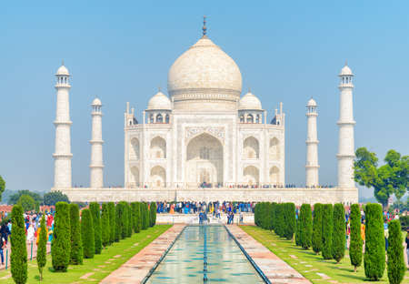 Colorful crowds of tourists walking along the Taj Mahal complex in Agra, India. Amazing view of the white marble mausoleum on blue sky background. Wonderful Mughal architecture.