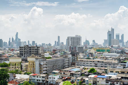 Wonderful Bangkok skyline, Thailand. Scenic view of old residential buildings and water towers in Pom Prap Sattru Phai district. Skyscrapers are visible on cloudy sky background. Amazing cityscape. Zdjęcie Seryjne - 125872095