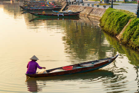 Vietnamese woman in traditional bamboo hat on wooden boat on the Thu Bon River at Hoi An Ancient Town at sunrise in Vietnam. Hoian is a popular tourist destination of Asia.