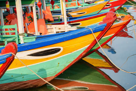 Closeup view of colorful traditional wooden Vietnamese tourist boats parked on the Thu Bon River in Hoi An Ancient Town (Hoian), Vietnam. Hoi An is a popular tourist destination of Asia. Zdjęcie Seryjne