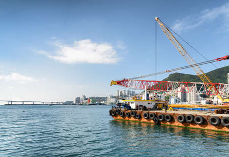 Crane vessel on blue sky background at the Port of Busan in South Korea. Busan City and Namhangdaegyo Bridge are visible in background. Zdjęcie Seryjne