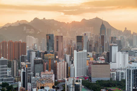 Gorgeous view of skyscrapers in downtown of Hong Kong. Victoria Peak is visible on sunset sky background. Beautiful cityscape. Hong Kong is popular tourist destination of Asia.
