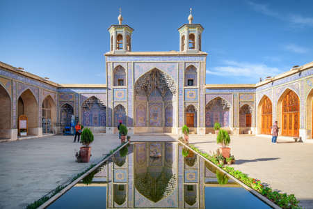 Gorgeous view of the Nasir al-Mulk Mosque (Pink Mosque) reflected in pool in the middle of traditional courtyard in Shiraz, Iran. Amazing Persian exterior of the Muslim place. Islamic architecture. Zdjęcie Seryjne