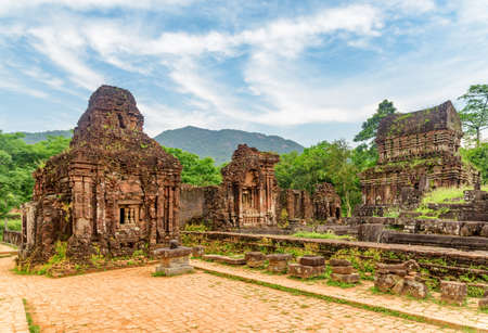 View of My Son Sanctuary among green woods in Da Nang (Danang), Vietnam. My Son is a complex of partially ruined ancient Hindu temples constructed by the kings of Champa. Zdjęcie Seryjne - 125873159