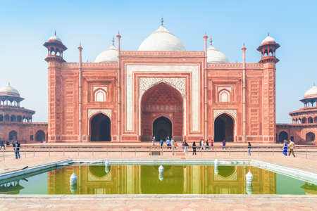 Awesome view of the Kau Ban Mosque of the Taj Mahal complex on blue sky background in Agra, India. Amazing red sandstone building reflected in water of pool. Wonderful Mughal architecture. Zdjęcie Seryjne