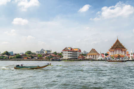 Traditional boat sailing along the Chao Phraya River in Bangkok, Thailand. Wat Kalayanamitr is visible on the shore. Beautiful view of the Buddhist temple from the river.