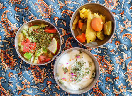Top view of traditional Iranian snacks. Fresh vegetable salad, yogurt and pickled vegetables. Awesome Persian cuisine. Zdjęcie Seryjne