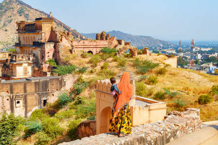 Jaipur, India - 12 November, 2018: Unknown Indian woman wearing traditional colorful sari holding child on scenic ruins background. Jaipur is a popular tourist destination of South Asia.