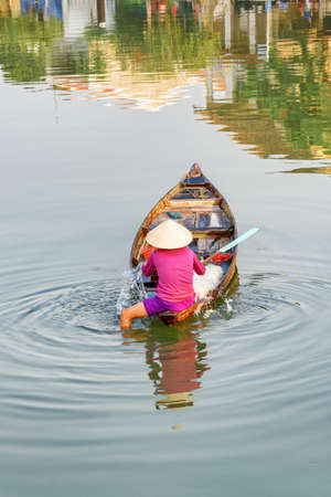 Scenic view of Vietnamese woman in traditional hat on wooden boat checking her fishing net on the Thu Bon River at Hoi An Ancient Town, Vietnam. Hoian is a popular tourist destination of Asia.