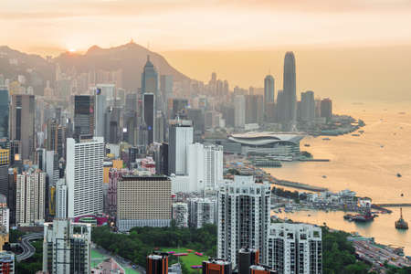 Beautiful view of the Hong Kong Island and Victoria harbor at sunset. Skyscrapers in downtown are visible on orange sky background. Scenic cityscape. Hong Kong is popular tourist destination of Asia.