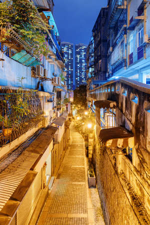 Beautiful night view of deserted narrow street at old town of Macau. Modern high-rise residential buildings are visible in background. Historic Centre of Macao is a popular tourist attraction of Asia. Zdjęcie Seryjne - 125873233