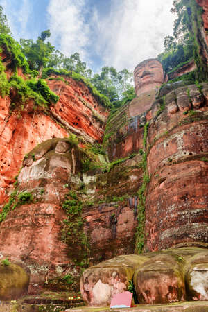 The Leshan Giant Buddha on blue sky background. Bottom view on sunny day. The largest and tallest stone Buddha statue in the world carved out of a red cliff at the Mount Emei Scenic Area in China. Zdjęcie Seryjne - 125873231