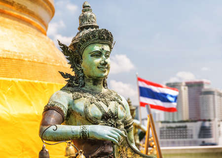 Scenic view of Buddhist statue at Wat Saket temple on the Golden Mount on sunny day. The flag of the Kingdom of Thailand fluttering over Bangkok is visible in background. Zdjęcie Seryjne - 125873239