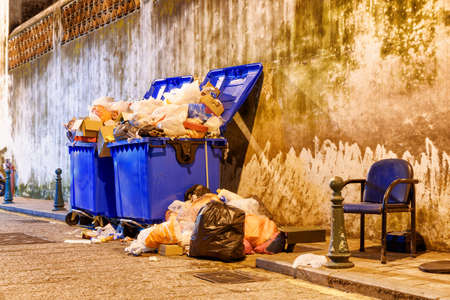 Overflowed garbage bins. View of trash cans on night street.