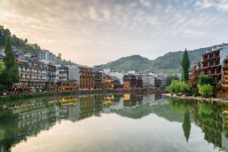 Fenghuang, China - September 22, 2017: Wonderful evening view of Phoenix Ancient Town. Traditional Chinese riverside buildings reflected in water of the Tuojiang River (Tuo Jiang River) at sunset. Publikacyjne