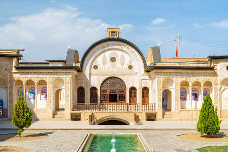 Kashan, Iran - 21 October, 2018: View of traditional Iranian courtyard with pool and fountains in the middle at Tabatabaei Historical House. Wonderful Persian architecture. Beautiful exterior.