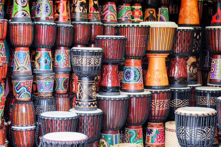 Fenghuang, China - September 22, 2017: Colorful wooden djembe drums at souvenir shop in Phoenix Ancient Town (Fenghuang). Fenghuang is a popular tourist destination of Asia. Publikacyjne
