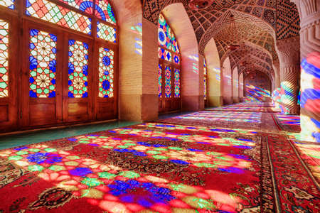 Gorgeous view of morning sunlight reflected through colorful stained glass windows on columns, the wall and the floor of prayer hall at the Nasir al-Mulk Mosque (Pink Mosque) in Shiraz, Iran. Redakční