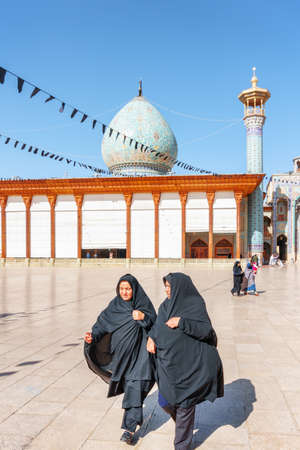 Shiraz, Iran - 29 October, 2018: Two Iranian women wearing black chadors crossing courtyard of the Shah Cheragh Mosque and Mausoleum. Gorgeous dome and minaret are visible on blue sky background.