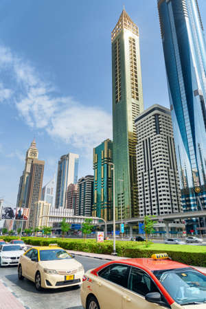 Dubai, United Arab Emirates - 2 November, 2018: Taxis parked at downtown. Scenic skyscrapers are visible on blue sky background. Amazing cityscape. Dubai is a popular tourist destination of UAE. Publikacyjne