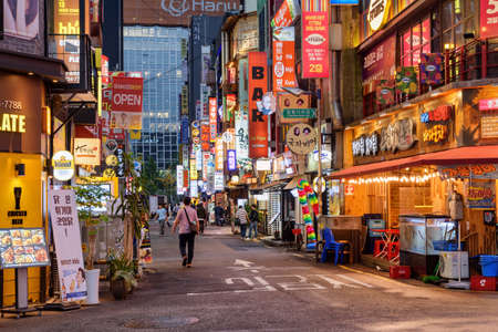 Seoul, South Korea - October 10, 2017: Evening view of illuminated colorful signboards on narrow street at downtown. Tourists and residents walking along bars and restaurants.