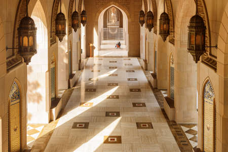 Muscat, Oman - 17 October, 2018: Arched passageway at the Sultan Qaboos Grand Mosque. Wonderful interior. Islamic architecture. The Muslim place is a popular tourist attraction of the Middle East.
