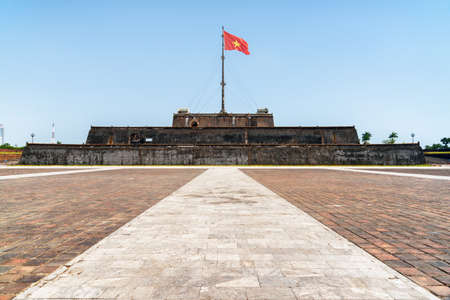 Wonderful view of a square and the flag of Vietnam (red flag with a gold star) fluttering over a tower of the Citadel on blue sky background in Hue, Vietnam. Within the Citadel is the Imperial City.