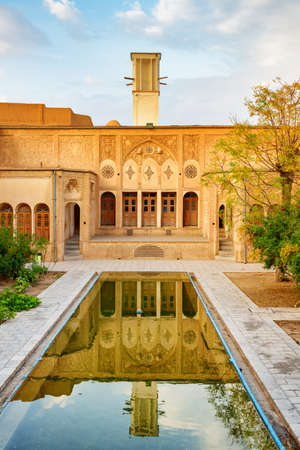 Amazing view of the Borujerdi Historical House in Kashan, Iran. Traditional courtyard with garden and pool in the middle. Windcatcher (badgir) is visible on blue sky background. Persian architecture.