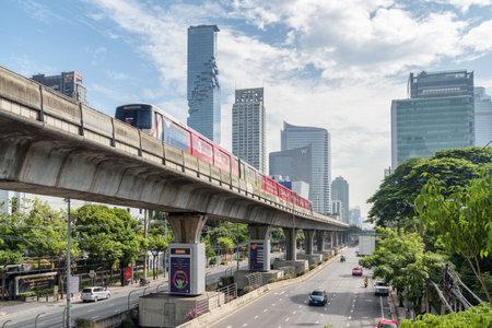 Bangkok, Thailand - 14 October, 2018: Skytrain passing above Sathon Road. Viaduct of BTS Silom Line. MahaNakhon Tower is visible on blue sky background. Amazing cityscape. Publikacyjne