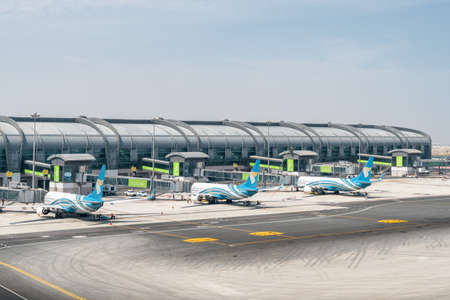 Muscat, Oman - 17 October, 2018: Three Oman Air aircraft parked on the apron of Muscat International Airport. The airport is the main base of the national airline. View of gates at departure area. Publikacyjne