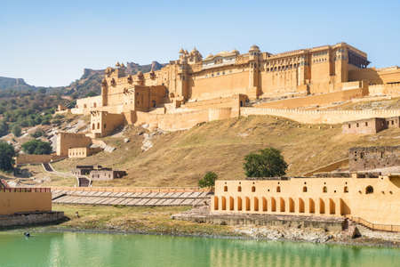 View of the Amer Fort and Palace (Amber Fort) and the Maota Lake in Jaipur, India. The Jaigarh Fort is visible on Aravalli Hill in background. Jaipur is a popular tourist destination of South Asia.