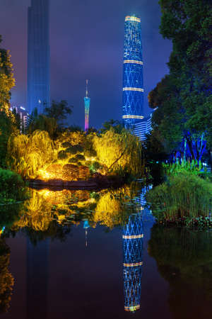 GUANGZHOU, CHINA - NOVEMBER 7, 2015: Beautiful night view of the Zhujiang New Town (Pearl River New Town) from park. The Canton Tower and the Guangzhou International Finance Centre reflected in pond. Publikacyjne