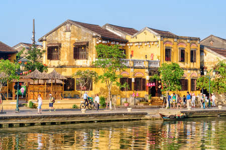 Hoi An (Hoian), Vietnam - April 11, 2018: Scenic view of traditional yellow building in Hoi An Ancient Town. Tourists walking along embankment of the Thu Bon River.
