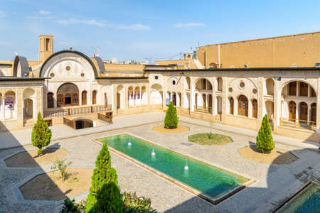 Kashan, Iran - 21 October, 2018: Scenic top view of traditional Iranian courtyard with pool and fountains in the middle at Tabatabaei Historical House. Persian architecture. Beautiful exterior.