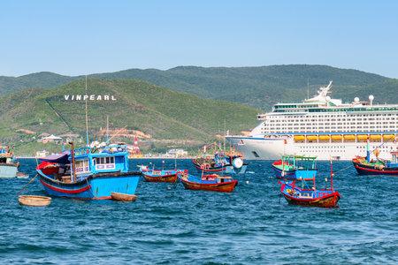Nha Trang, Vietnam - September 20, 2015: Amazing view of cruise ship and traditional Vietnmese fishing boats at Nha Trang Bay. The Hon Tre Island is visible on blue sky background. Publikacyjne