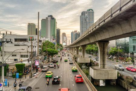 Bangkok, Thailand - 15 October, 2018: Beautiful view of Sathon Road at sunset. Street traffic of Bangkok. Viaduct of Silom Line and modern buildings. Wonderful cityscape. Publikacyjne