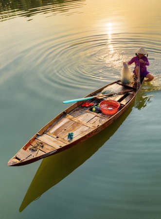 Hoi An (Hoian), Vietnam - April 12, 2018: Awesome top view of Vietnamese woman in traditional bamboo hat on wooden boat checking her fishing net on the Thu Bon River at Hoi An Ancient Town at sunrise.