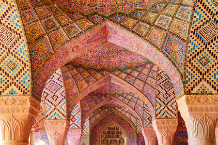 Shiraz, Iran - 29 October, 2018: Fabulous view of vault ceiling covered colorful mosaic inside the Nasir al-Mulk Mosque (Pink Mosque). Amazing Persian interior of the Muslim place.